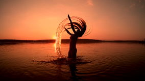 Silhouette of young girl splashing in the water stock footage