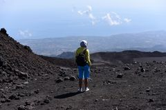 A silhouette of a girl stanging on a slope of Etna - the highest active volcano in Europe stock image