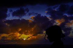Silhouette of a young girl with sunrise over the ocean in background Stock Image