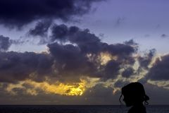 Silhouette of a young girl with sunrise over the ocean in background Royalty Free Stock Photos