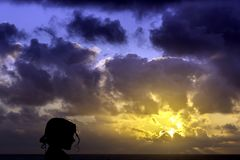 Silhouette of a young girl with sunrise over the ocean in background Royalty Free Stock Photo