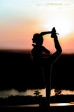 Silhouette of a young girl on the sunset background. Young girl practicing yoga in the rays of the setting sun Stock Photography