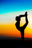 Silhouette of a young girl on the sunset background. Young girl practicing yoga in the rays of the setting sun Stock Photo