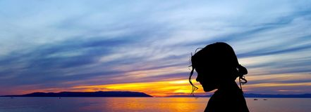 Silhouette of a young girl with sunset over the Adriatic Sea in background in Makarska, Croatia Royalty Free Stock Photo