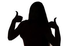 Silhouette of young girl with thumbs Stock Photo
