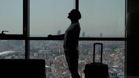 Silhouette of young girl traveler with suitcase is entering in hotel room with panoramic city view.