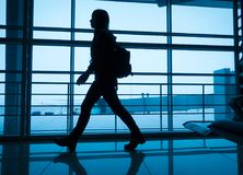 Silhouette of girl walking on airport terminal. Silhouette of young girl walking on window of airport terminal with small backpack, blue toned image Royalty Free Stock Photography