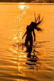 Silhouette of young girl in the water that splashing their hair Stock Photo