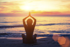 Silhouette of young girl in yoga pose sitting on the beach. During sunset Stock Photography