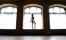 Silhouette of a young good shaped ballerina standing on the huge window. Concept of healthy and beauty