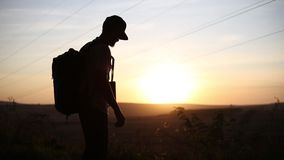 Silhouette of young guy on a hiking, using laptop for searching coordinates.