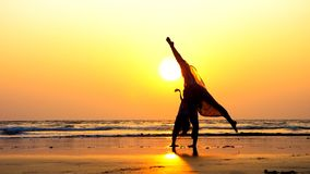 Silhouette of young gymnast woman doing handspring on sandy beach at sunset stock image