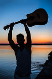 Silhouette of young handsome man holding guitar at seaside during sunrise. Silhouette of young handsome man holding guitar at seaside at sunrise. Copy space Royalty Free Stock Images