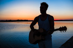Silhouette of young handsome man playing guitar at seaside during sunrise. Royalty Free Stock Image