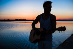 Silhouette of young handsome man playing guitar at seaside during sunrise. Stock Images