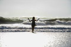 Silhouette of young happy Asian woman relaxed looking at wild sea waves on sunset tropical beach Royalty Free Stock Photos