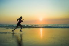 Silhouette of young happy and attractive African American runner woman exercising in running fitness sprint workout at beautiful b stock photography
