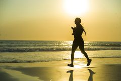 Silhouette of young happy and attractive African American runner woman exercising in running fitness workout at beautiful beach jo royalty free stock image