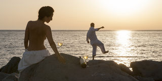 Silhouette of young happy couple having fun on beach rocks. At sunrise Stock Images