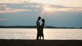 Silhouette of young happy couple hugging on the shore of the river in evening. Man and woman spending time on the beach. stock video