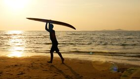 Silhouette of young happy surf man running with long surf boards at sunset on tropical beach. surfer on the beach in sea shore. At sunset time with beautiful stock video footage