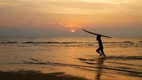 Silhouette of young happy surf man running with long surf boards at sunset on tropical beach. surfer on the beach in sea shore. At sunset time with beautiful stock video