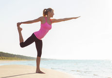 Silhouette of young healthy and fit woman practicing yoga Stock Photo