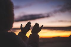 Silhouette of young human hands open palm up worship and praying to god at sunrise, Christian Religion concept background.  royalty free stock photo