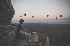 Silhouette of young male backpacker sitting and watching hot air balloon travel destinations in Bagan, Myanmar. Silhouette of young male backpacker sitting and Royalty Free Stock Photos