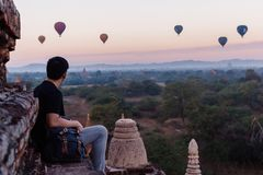 Silhouette of young male backpacker sitting and watching hot air balloon travel destinations in Bagan, Myanmar.  Stock Photo