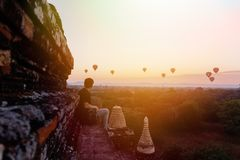 Silhouette of young male backpacker sitting and watching hot air balloon travel destinations in Bagan, Myanmar. Silhouette of young male backpacker sitting and stock photography