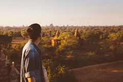 Silhouette of young male backpacker watching sunset and pagoda in Bagan, Burma. Stock Photography