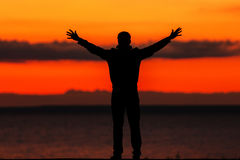 Silhouette of a young man against the background of the crimson sunset. Crimson sunset` `a young man stands on the shore with open arms Stock Photos