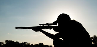Silhouette of a young man aiming with a long rifle. Against setting sun Royalty Free Stock Photography