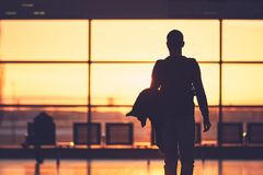 Airport terminal at the sunset. Silhouette of the young man at the airport. Traveler leaves to the gate during golden sunset Stock Photos