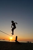 Silhouette of young man balancing on slackline at Stock Images