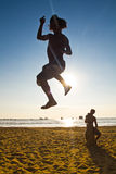 Silhouette of young man balancing on slackline at Royalty Free Stock Photo