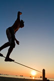 Silhouette of young man balancing on slackline at Stock Photography