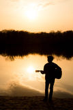 Silhouette of a young man on the beach with a guitar Stock Photos