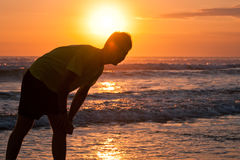 Silhouette of young man on the beach. With ocean view at the sunset Stock Photography