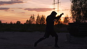 Silhouette of young man boxer training for kicking on sunset at city park. Silhouette of young man boxer training for kicking on sunrise at city park stock footage