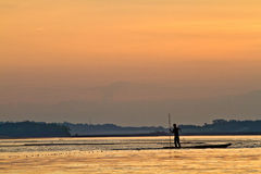 Silhouette of young man in a canoe along the Napo. Silhouette of a young man in a canoe along the Napo river in the amazon rainforest during sunset, Yasuni Stock Photography