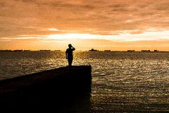 Silhouette of young man on the concrete pier Royalty Free Stock Photo