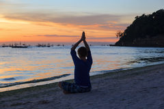 Silhouette of young man doing yoga at sunset Royalty Free Stock Image