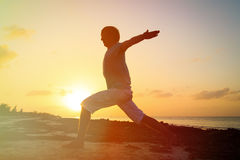 Silhouette of young man doing yoga at sunset Royalty Free Stock Photo