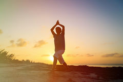 Silhouette of young man doing yoga at sunset Royalty Free Stock Images