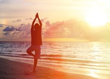 Silhouette of young man doing yoga at sunset Stock Image
