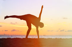 Silhouette of young man doing yoga at sunset Royalty Free Stock Photography