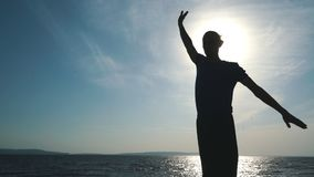 Silhouette of young man doing yoga at sunset beach. Man silhouette doing yoga exercise at sunset beach stock footage