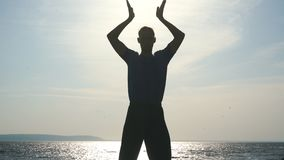 Silhouette of young man doing yoga at sunset beach. Man silhouette doing yoga exercise at sunset beach stock video footage